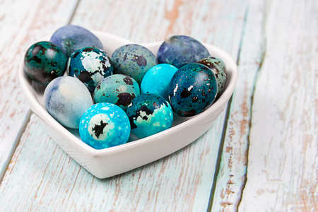 Easter blue quail eggs in a plate in the shape of a heart on a wooden table. Foto de archivo