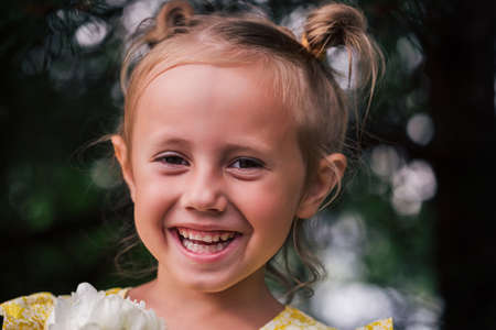 The caucasian child of 6 years is a beautiful girl with wide eyes, look at the camera. Expressive facial emotions