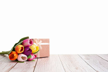 Present box and tulips on wooden rustic table with white background with space for text.