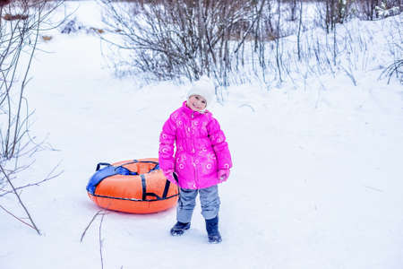 Little girl drags slide-slide cheesecake up snowy hill. Concept of winter outdoors activities for children.