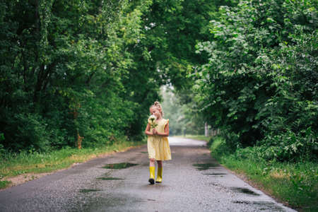 Portrait of caucasian girl of 6 years in yellow dress and rainboots standing in the park holding peony flower