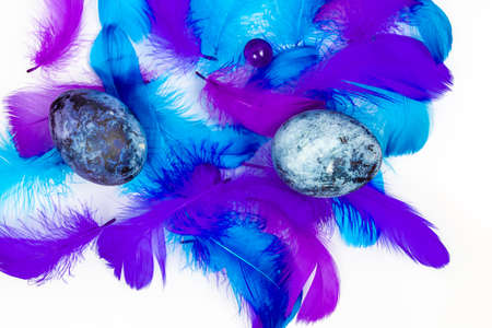 Blue Easter eggs and small fluffy blue feathers randomly scattered on white table
