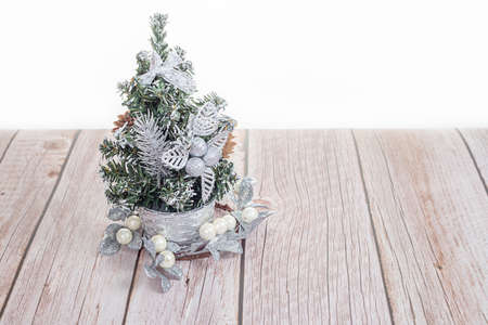 Cute little Christmas tree on wooden table on white background Foto de archivo