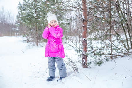 Cute girl in pink warm clothes playing in the winter forest, spending time outdoors in winter Foto de archivo