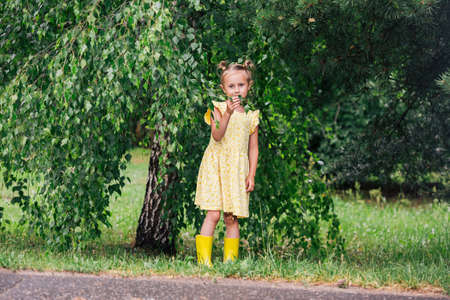 Portrait of caucasian girl of 6 years in yellow dress and rainboots standing in the park