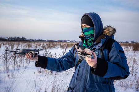Caucasian Male in the blue jacket launching a flying drone with a remote controller in his hand on winter field.