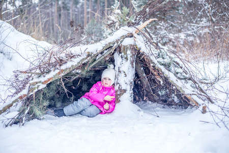 Little girl in warm clothes plays in a hut from coniferous branches in the winter forest, spending time outdoors in winter