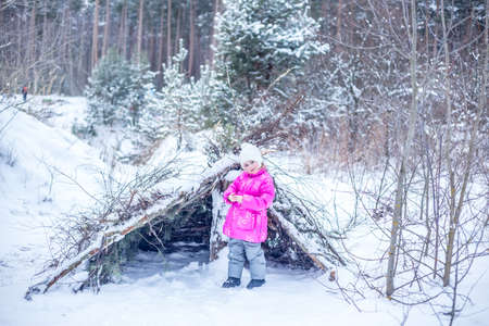 Little girl in warm clothes builds a hut from coniferous branches in the winter forest, playing outdoors in winter Foto de archivo
