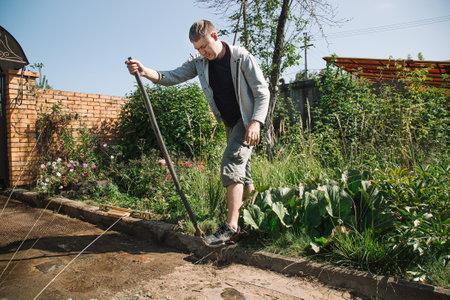 Man lays curbstone for grouting garden path, construction work on garden plot Foto de archivo