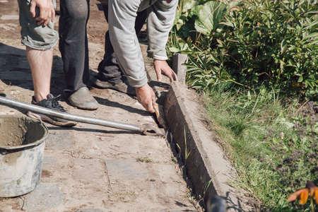 Men lay curbstone for grouting garden path, construction work on garden plot