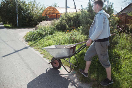 A man carries a garden wheelbarrow for loading sand to fill the paths