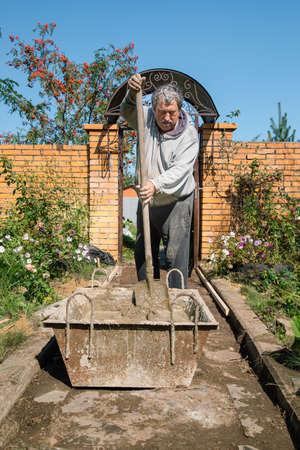 Eldery man kneads cement for pouring a garden path, garden construction work