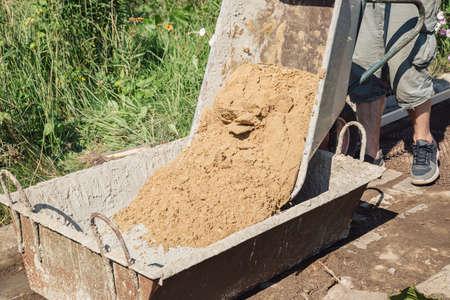 Uploading sand into a cement mixture for pouring a garden path Foto de archivo