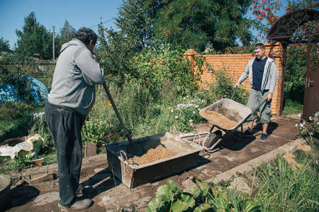 Eldery man kneads cement for pouring a garden path