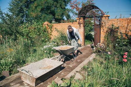 A man unloads sand into a cement mixture for pouring a garden path Foto de archivo