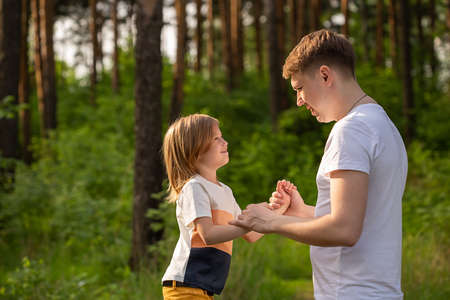 Caucasian girl of 6 years holding dad's hand looking at each other in the forest. Father and daughter playing together, laughing and having fun. Happy Family activity concept