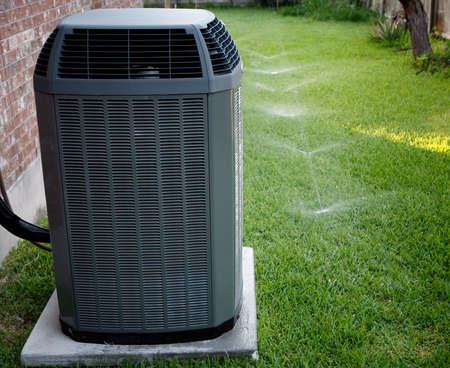 heat home: Modern air conditioner on backyard with working sprinkler system Stock Photo