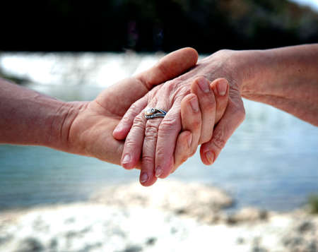 sick person: Young hand supporting old hand-helping elderly people concept