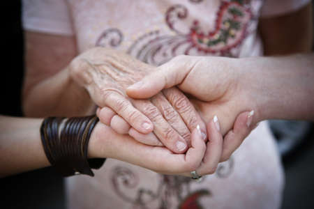 adult care: helping elderly people concept - young hands supporting old hand