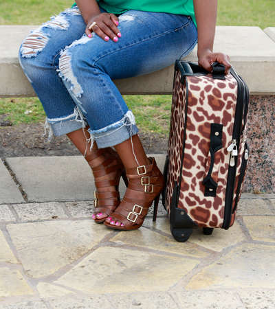 suit case: Traveling concept: AfricanAmerican woman and suitcase Stock Photo