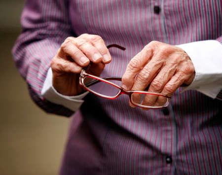 artritis: Manos de mujer de edad avanzada con la celebración de la artritis vasos Foto de archivo