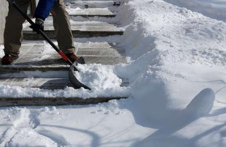 Man shoveling the show on bright winter day Standard-Bild