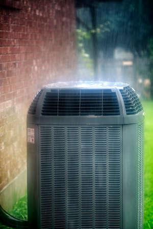bomba de agua: Moderno acondicionador de aire bajo la lluvia Foto de archivo