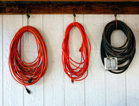 Extension power cords on the wall of working shop 版權商用圖片