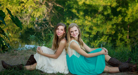 Outside portrait of beautiful sisters-teenagers