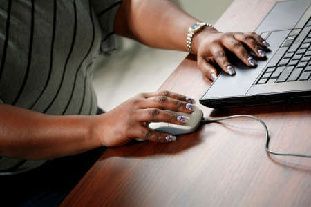 african business: Hands of African-American woman with beautiful manicure working on computer