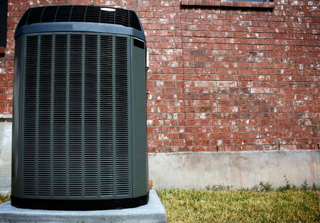 High efficiency modern AC-heater unit, energy save solution in front of brick wall Stock Photo