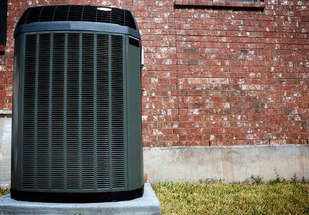 Unità di riscaldamento AC ad alta efficienza moderna, soluzione di risparmio energetico davanti al muro di mattoni Archivio Fotografico