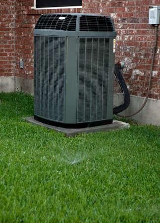 Moderno condizionatore d'aria in cortile con impianto di irrigazione di lavoro