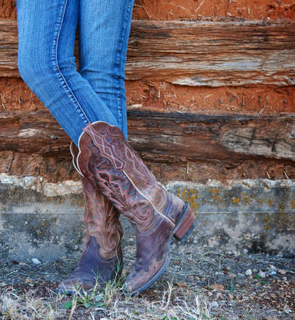 botas: imagen de estilo occidental de las piernas de vaquera en jeans y botas sobre fondo de la pared abandonada Foto de archivo
