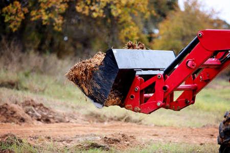 front end loader: Tractor front end loader with dirt on construction side