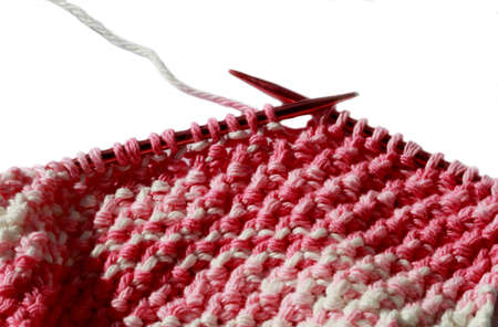 Handmade knitting fabric on needles isolated on white