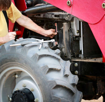 Man repairs large red tractor with focus on tools and front wheel