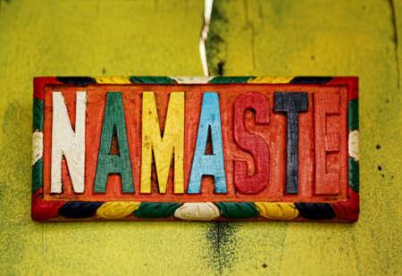 Colorful sign NAMASTE – the Sanskrit salutation - on old rustic wall