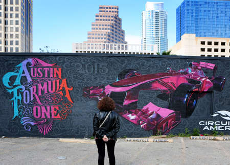 March, 2017, Austin, Texas. Tourist looking at Austin Formula One Mural with downtown on background. 新聞圖片