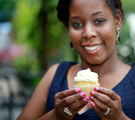 Close up of African American womens hands holding cupcake - selective focus on cupcake
