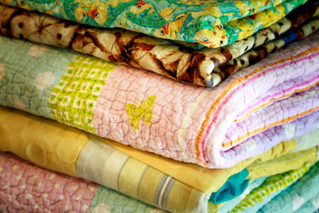 Stock of colorful old washed blankets folded after laundry.