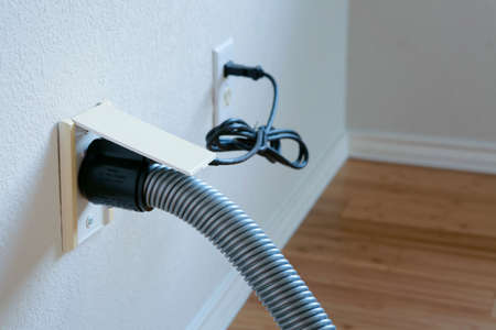 Central vacuum cleaner hose connected to the wall.
