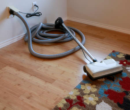 Cleaning contest: Beautiful bamboo hardwood floor and wool rug with a central vacuum cleaner attached to the wall Stockfoto