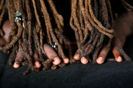Conceptual image of Hands of African-American man and dreadlocks