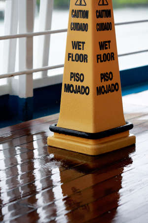 bilingual: Sign showing warning of caution wet floor in English and Spanish. It is raining... Stock Photo