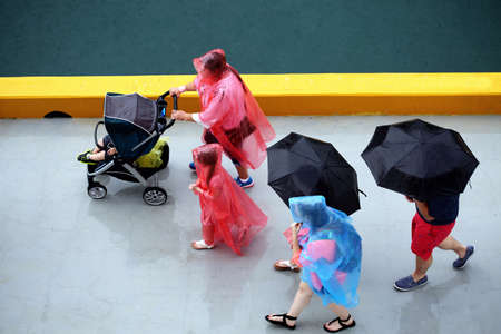 Top view of family walking under rain, covered with umbrellas, rain jackets and stroller roof.