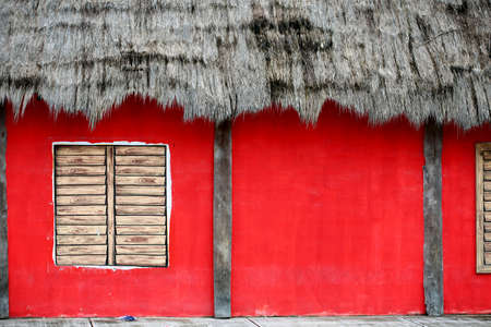 Painted wall with painted window and old fashion palm leaf roof