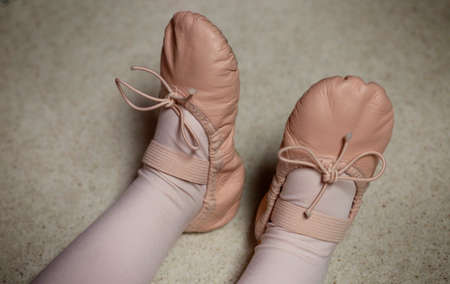 Classical ballet school: legs of little ballerina in ballet shoes