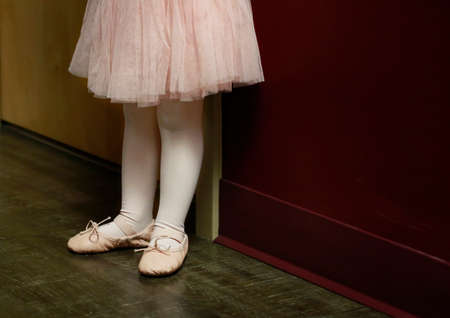 Classical ballet school: legs of little ballerina in ballet shoes at the wall