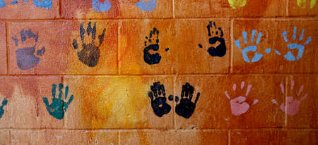 Background of colorful children hand prints on the wall